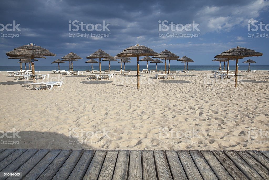 Different parasols and sun loungers on the empty beach stock photo