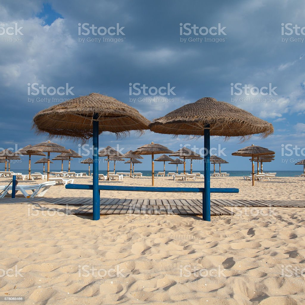 Different parasols and sun loungers stock photo