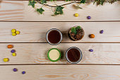 Different pastries with tea on a light wooden background.