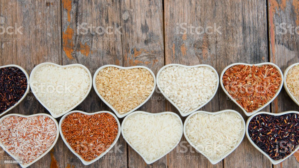 Different rice in ceramic bowl hearth shape for background stock photo