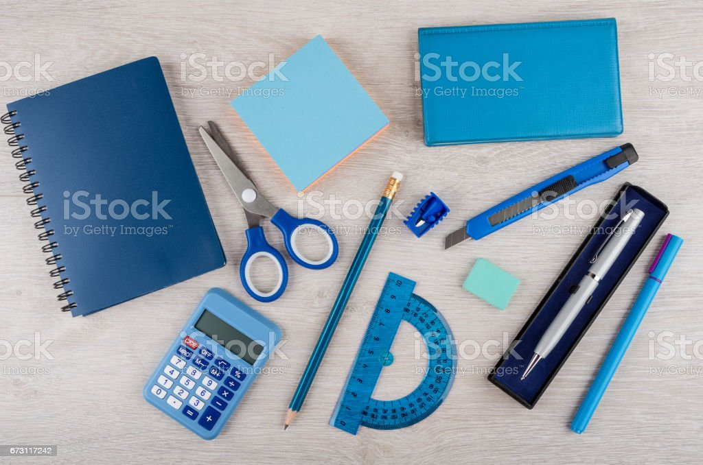 Different stationery tools of blue color on light wooden table stock photo