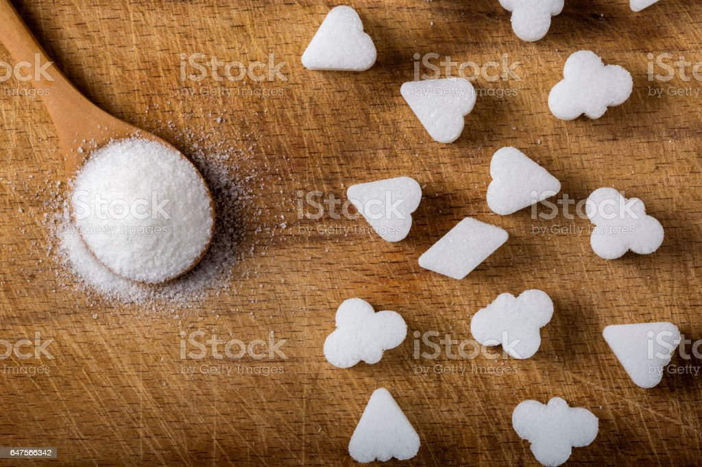 Different sugar cubes shapes and wooden spoon filled with sugar stock photo