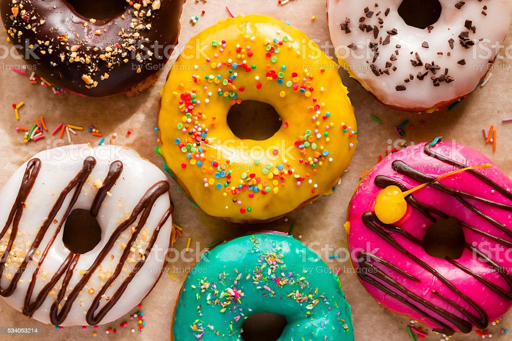 Different tasty donuts on a background of paper stock photo