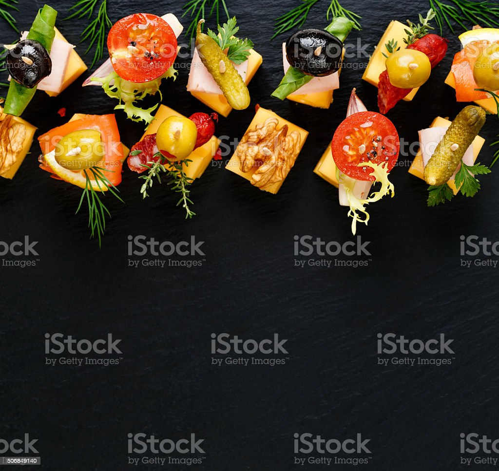 Different types of cheese skewers on a dark background stock photo