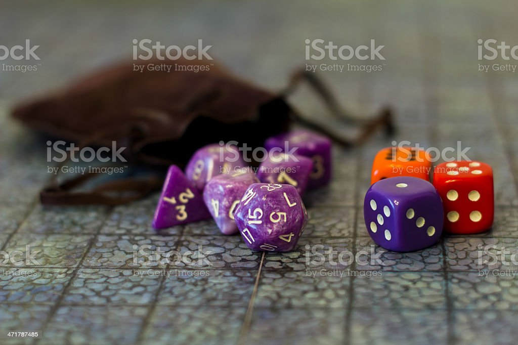 Different types of dice and a brown suede bag on the floor stock photo
