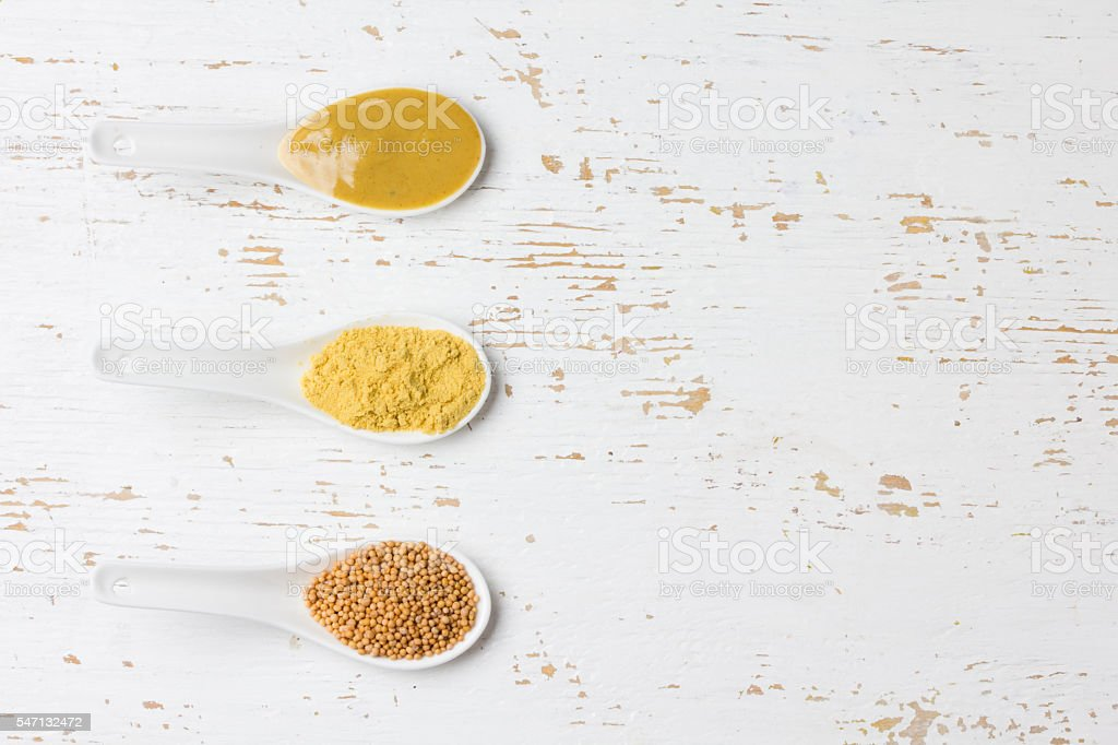Different types of mustard: powder, seeds, spicy cream. Top view stock photo
