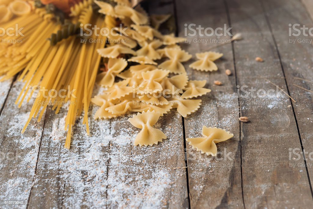 Different types of pasta on wooden background stock photo