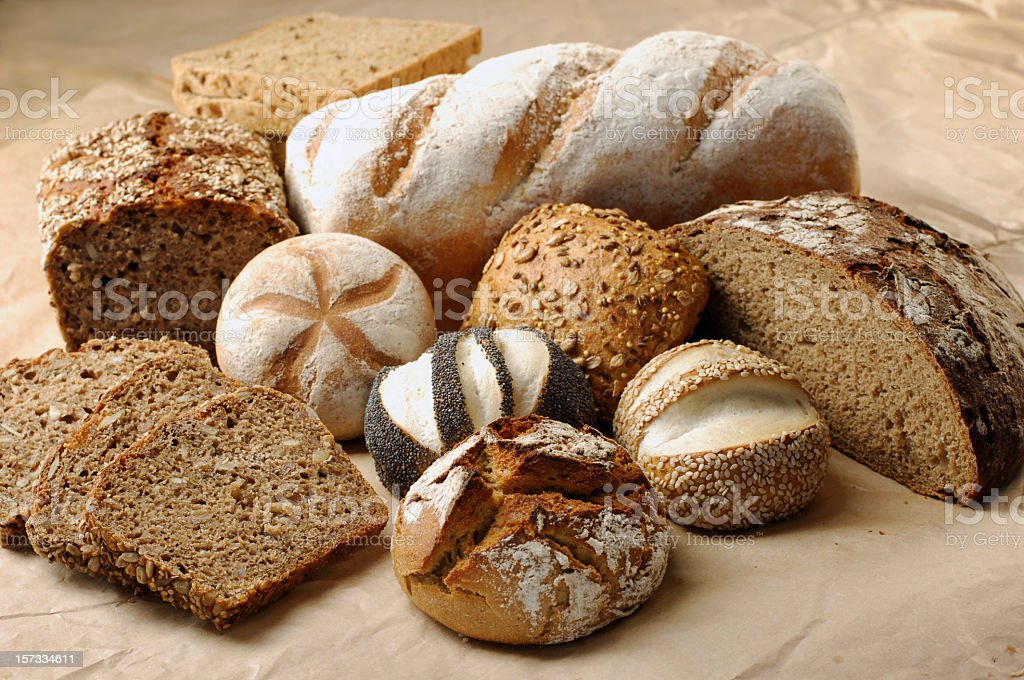 Different types of whole wheat bread on a wood surface royalty-free stock photo