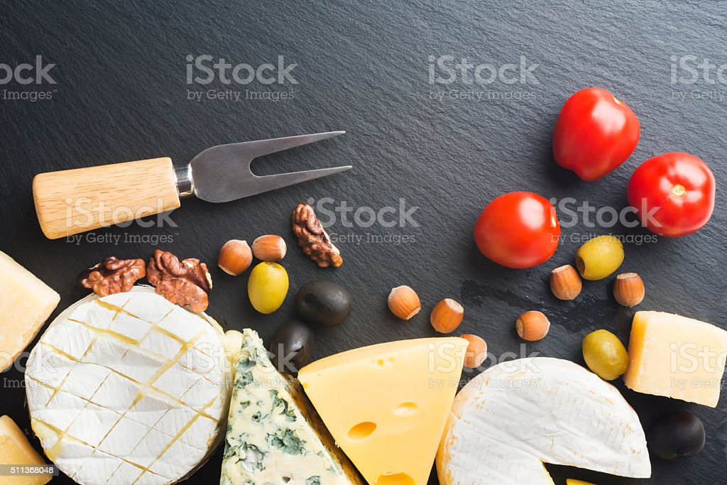 Different varieties of cheese on a black board stock photo