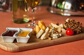 different varieties of cheese with honey and jam on tray