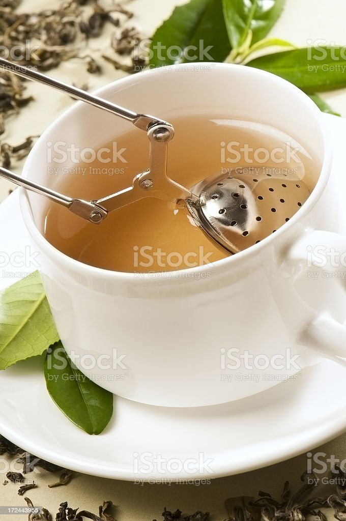 Diffuser of Green tea leaves in white cup and saucer stock photo