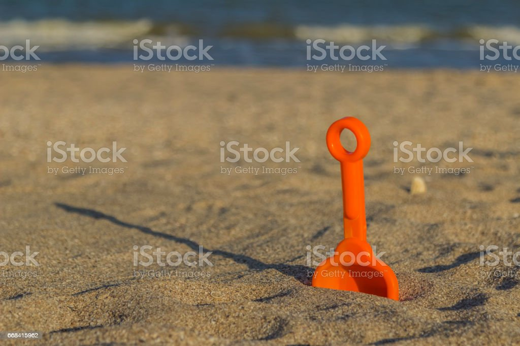Digged into the sand shovel on beach stock photo