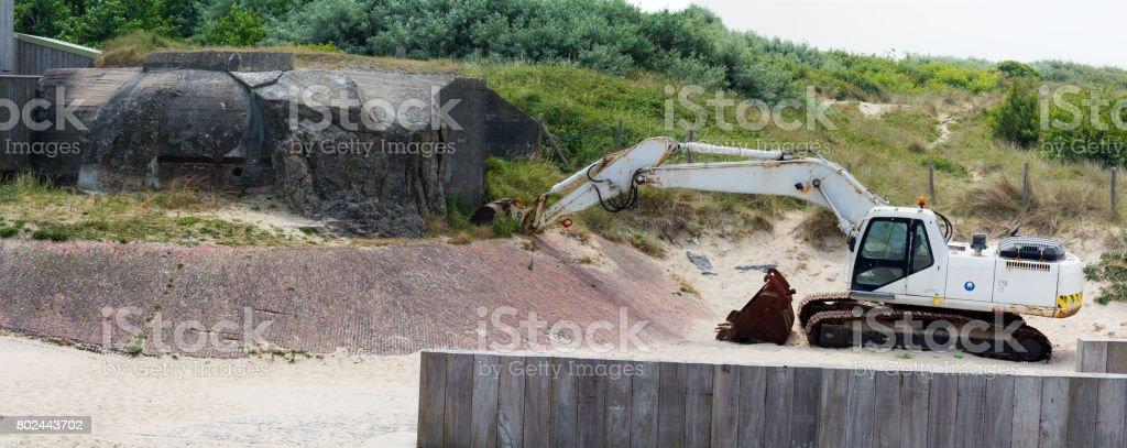 Digger demolishing fortification of the german world war ii atlantic wall stock photo