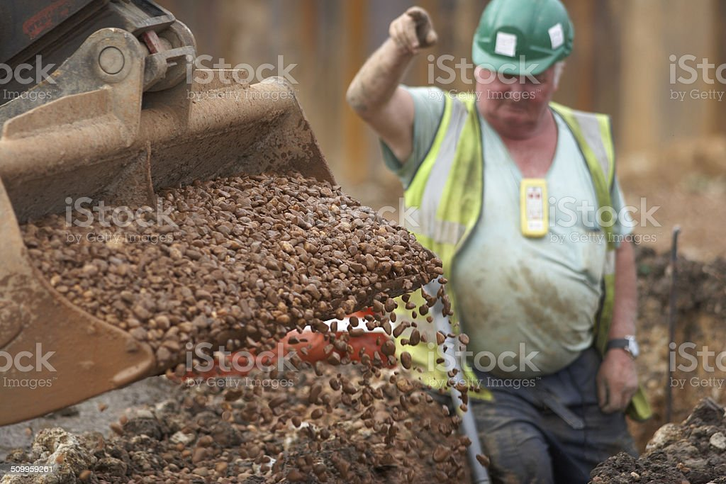 Digger Filling Ditch With Gravel On Construction Site stock photo