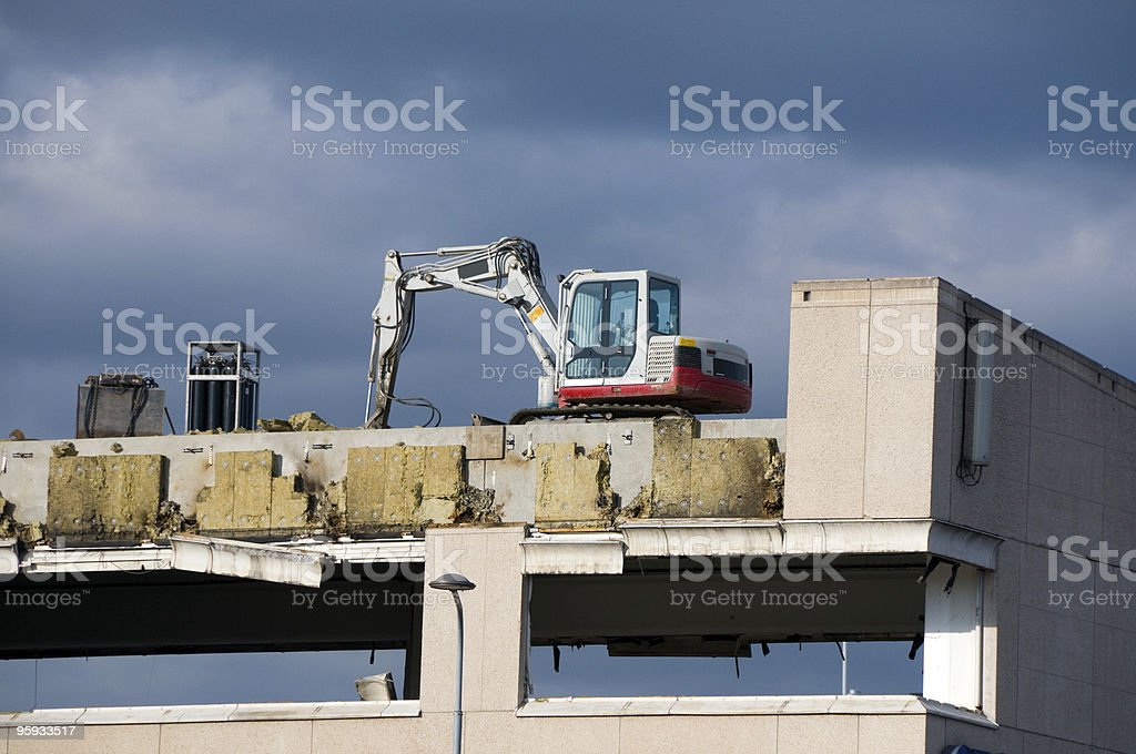 Digger on rooftop against dramatic sky stock photo