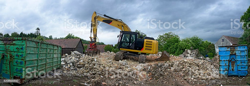 digger with a picker arm on a mountain of rubble stock photo