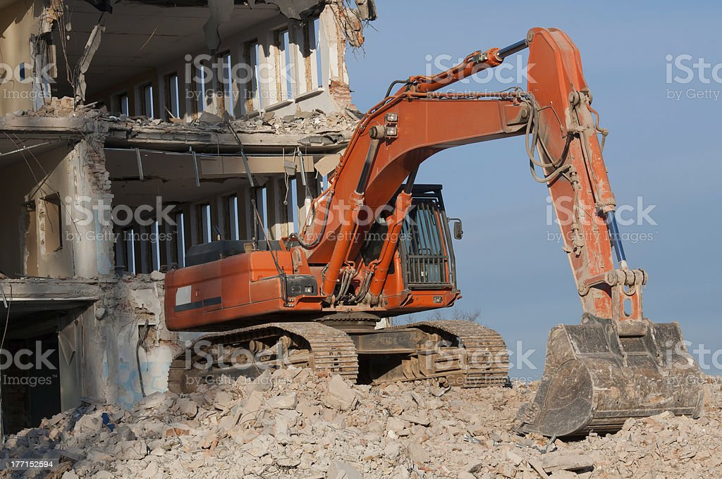 digger working during demolition of the building royalty-free stock photo