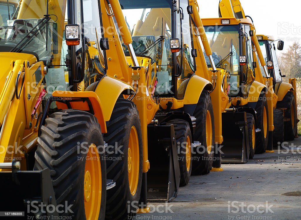 Diggers in a Row on Industrial Parking Lot stock photo