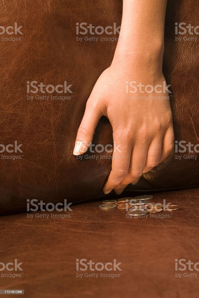 Digging for change in couch cushions stock photo