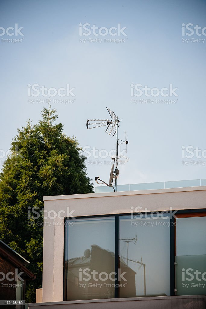 Digital and analog antenna next to satellite dish on roof stock photo