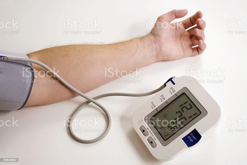Digital blood pressure machine taking blood pressure of man royalty-free stock photo