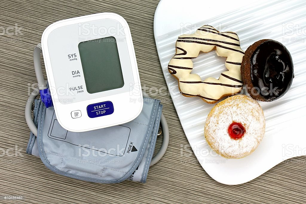 Digital Blood Pressure Monitor and Donut, Unhealthy food, High sugar. stock photo