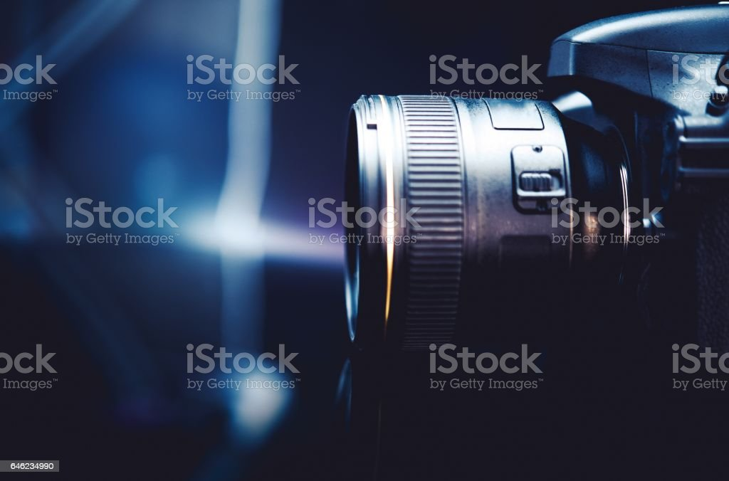 Digital Camera and the Photography Concept Photo. Dark Blue Color Grading with Little of Light. Camera Side View. stock photo