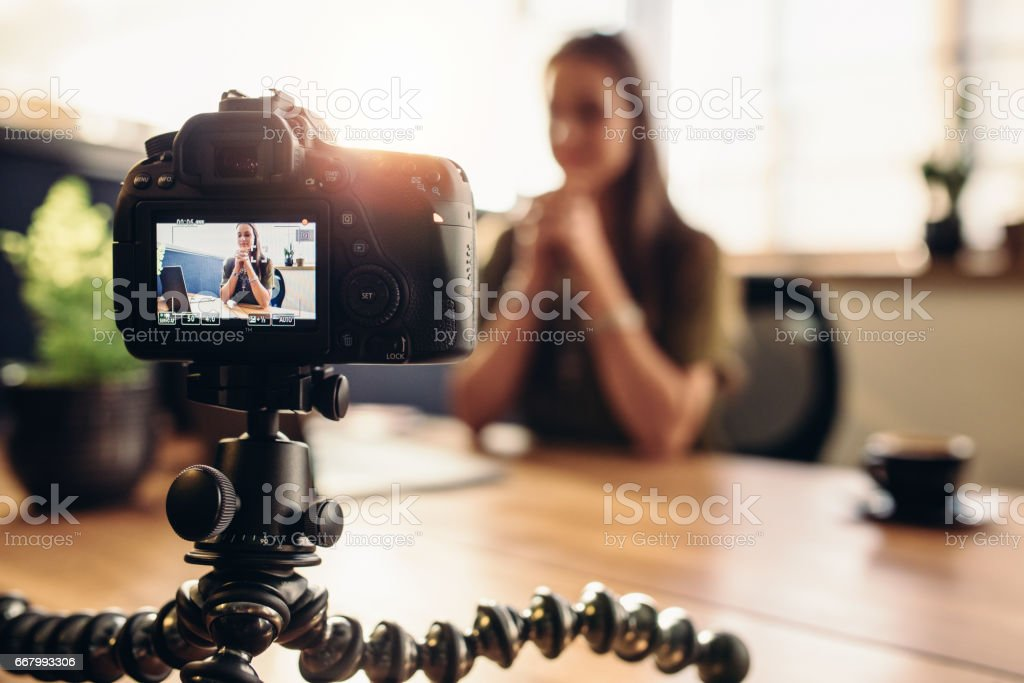 Digital camera on flexible tripod recording a video of woman at desk. stock photo