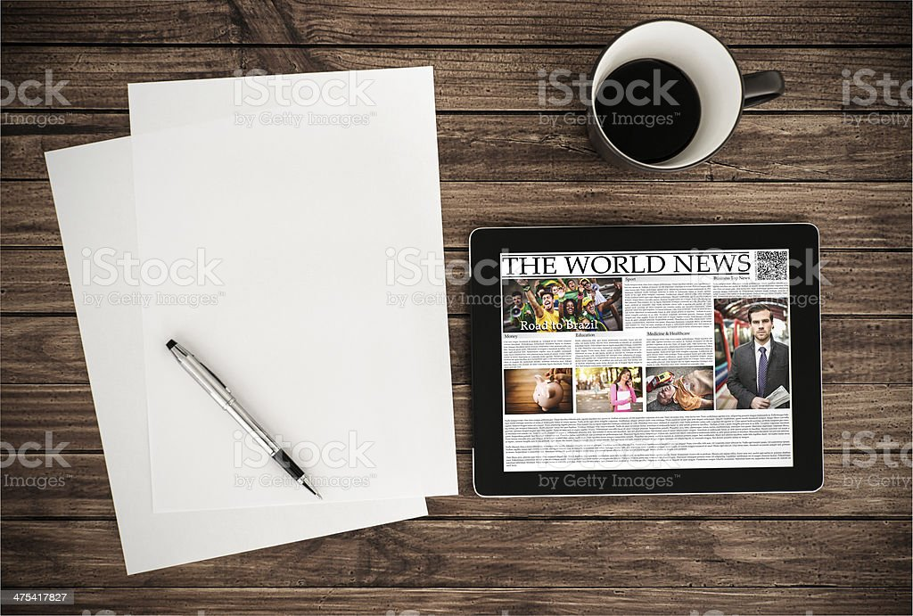 digital ebook reader with newspaper on wood table stock photo