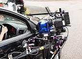 Digital film camera on set, on car mount.