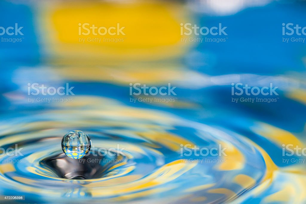 Digital image of blue and yellow swirling water with a drop stock photo