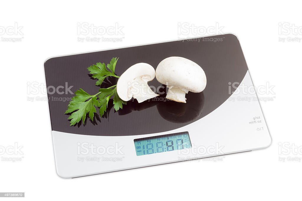 Digital kitchen scale with mushrooms on light background stock photo