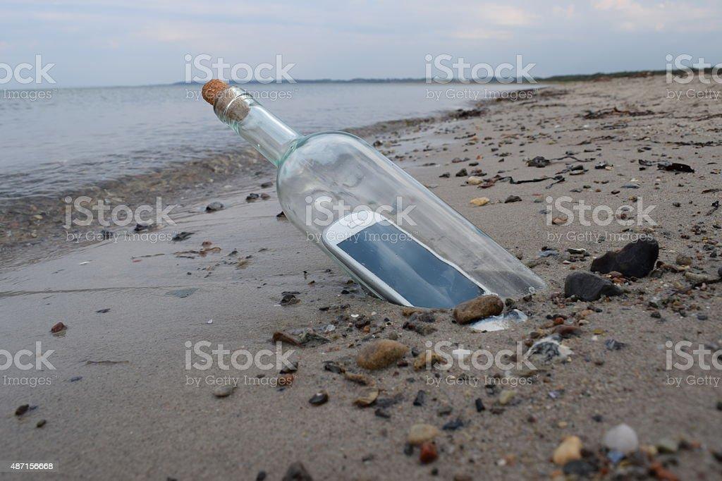 Digital native castaway sending a help message in a bottle stock photo