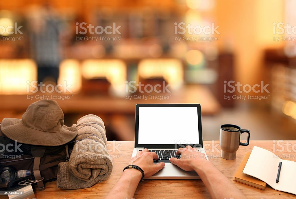 Digital nomad backpacker working with laptop from a cafeteria stock photo