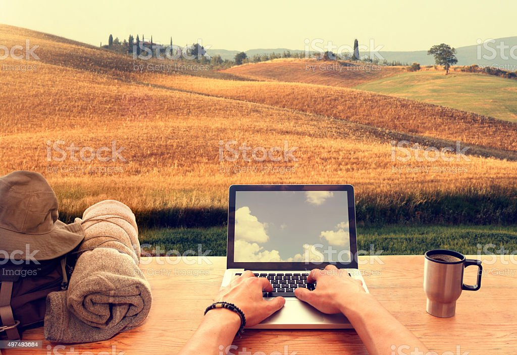 Digital nomad using laptop computer from an hillside italian town stock photo