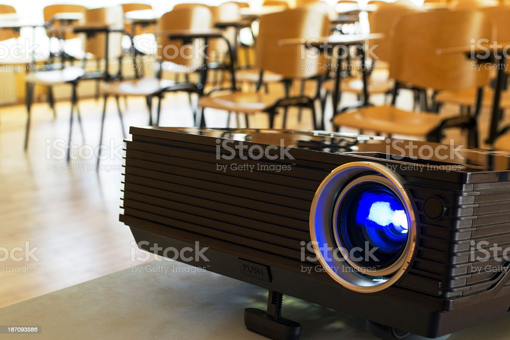 A digital projector in front of desks in a classroom stock photo
