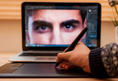 Digital retoucher retouching a photo with pen tablet