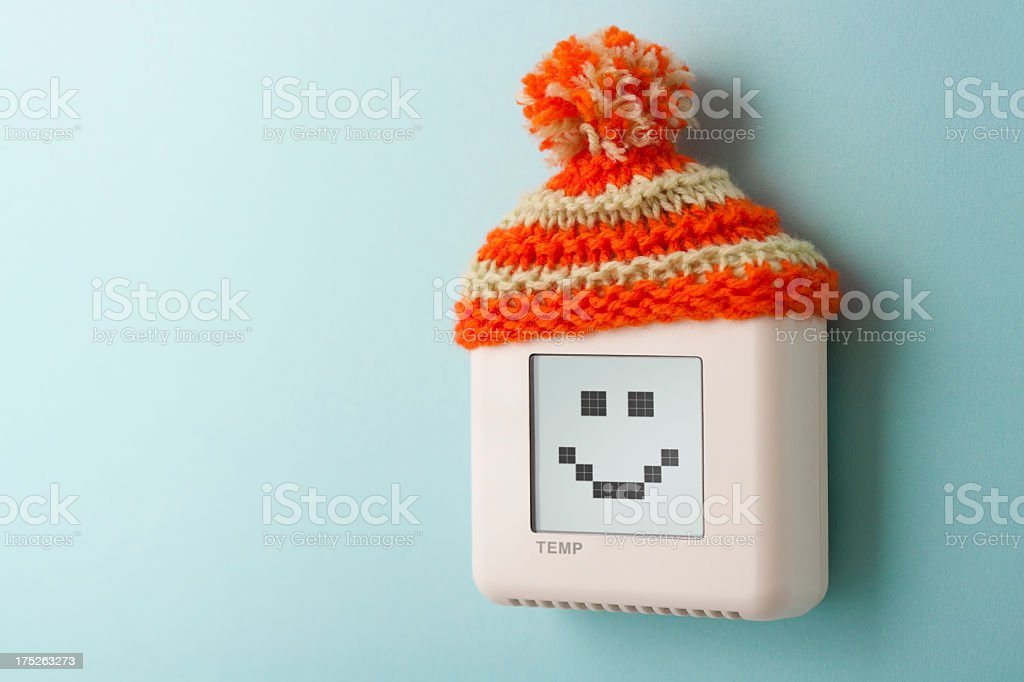 Digital room temperature thermostat with smiley face and wooly hat stock photo