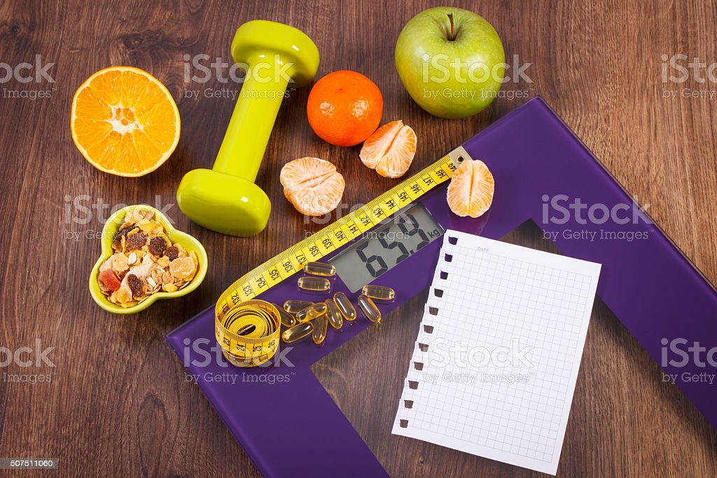 Digital scale with tape measure, tablets, dumbbells, fruits, muesli stock photo