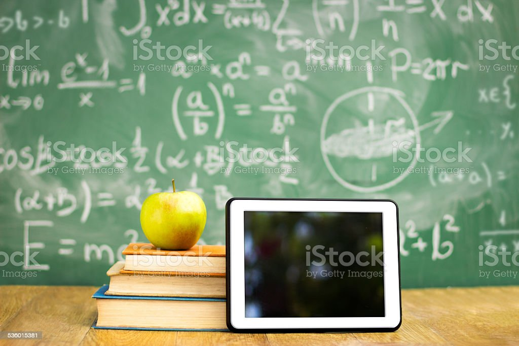 Digital tablet and apple on stack of books stock photo