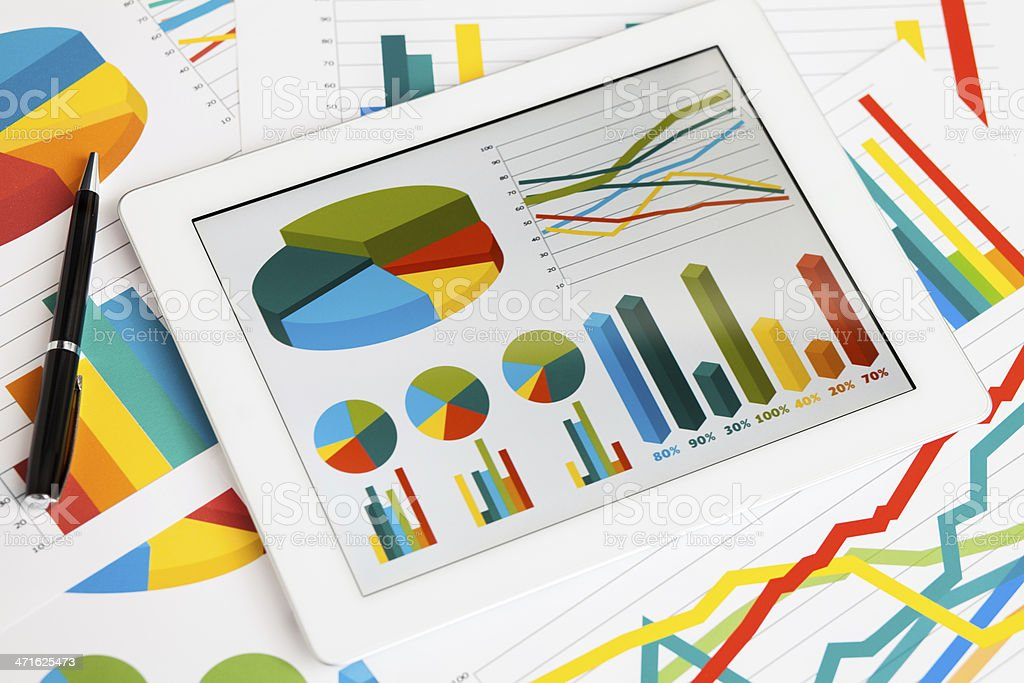 Digital tablet and business graphs stock photo