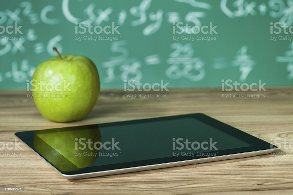 Digital tablet and green apple on a wooden desk stock photo