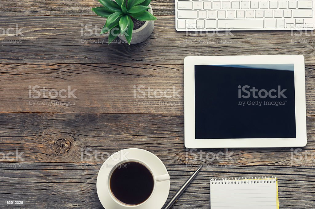 Digital tablet and keyboard on a wooden table. stock photo