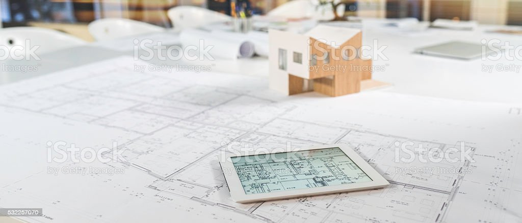 Digital tablet, blueprint and model house on a table stock photo