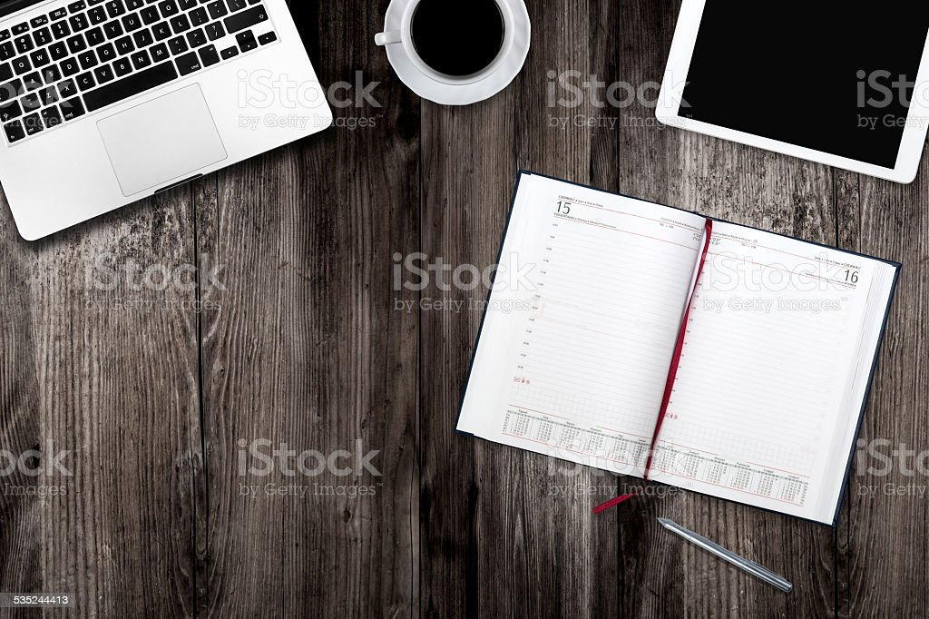 digital tablet , computer and cup of coffee on wooden table stock photo