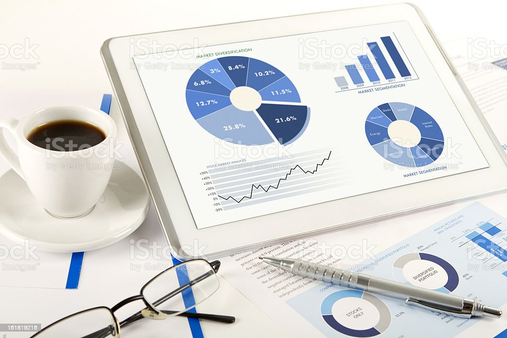 Digital tablet financial analysis with coffee cup stock photo