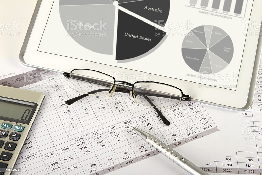 Digital tablet financial workflow with glasses and pen royalty-free stock photo