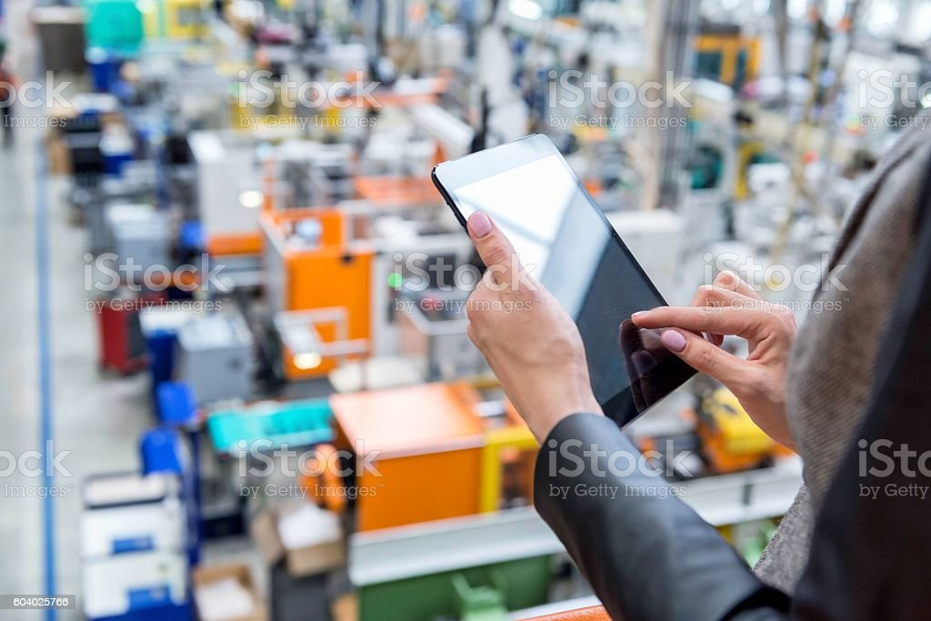 Digital tablet & Futuristic factory stock photo