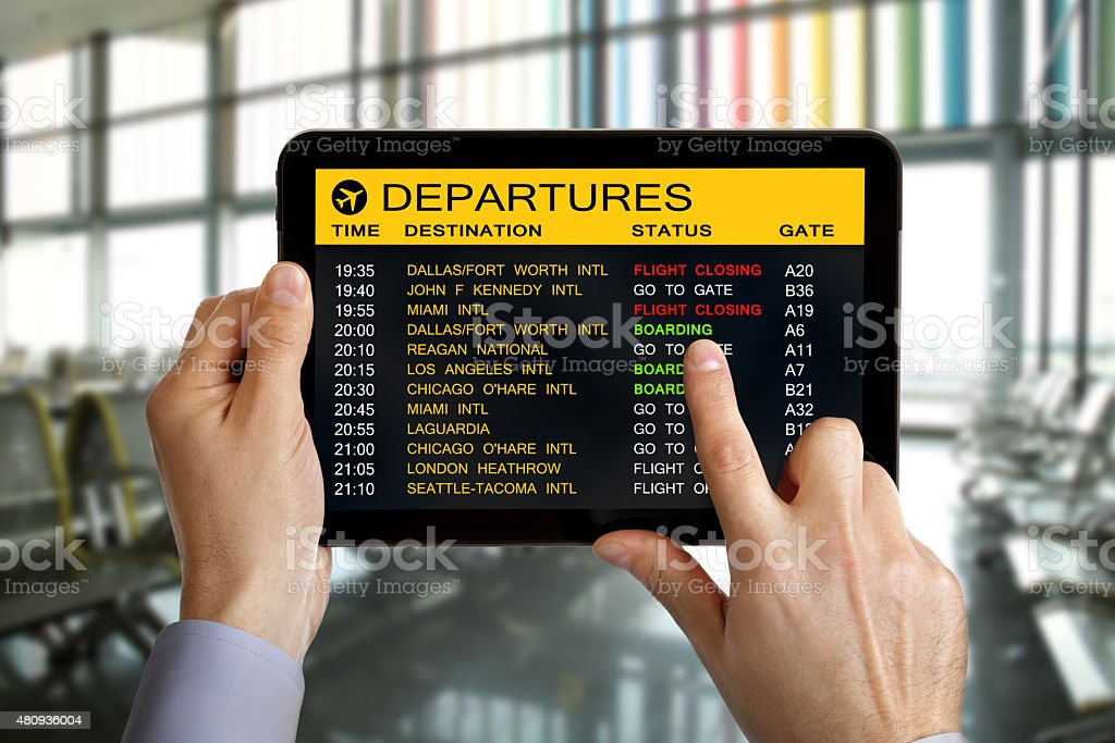 Digital tablet in airport with flight information stock photo