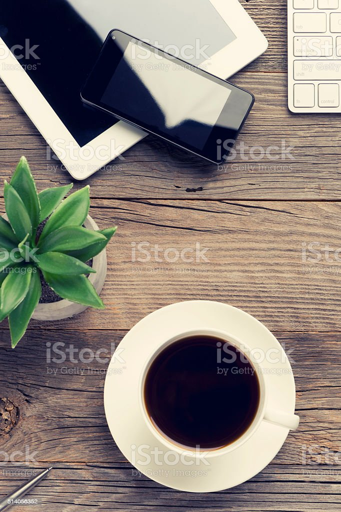 digital tablet, mobile phone and keyboard on wooden table. stock photo